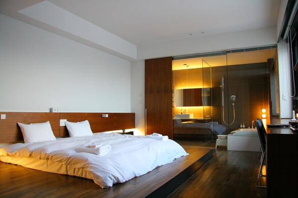 Phòng ngủ với những vật dụng nội thất bằng gỗ sang trọng và nhà vệ sinh vách kính hiện đại